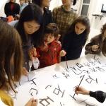Nie Min mostra ai bambini la scrittura cinese