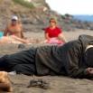 Un uomo sulla sabbia. Dietro, famiglia in un momento di relax